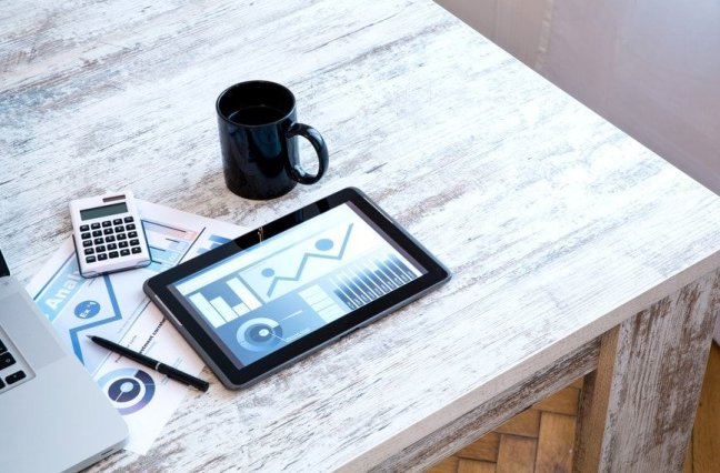 Coffee mug and iPad on desk