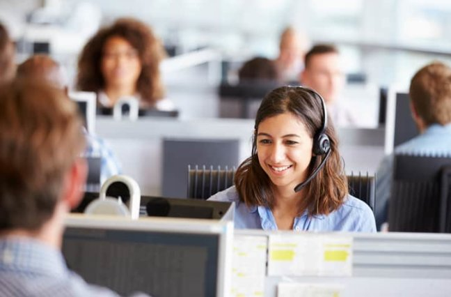 happy call center agent in middle of large call center