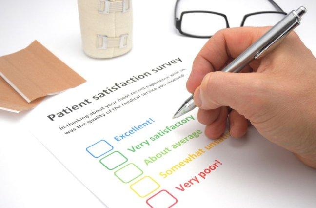Mans hand filling out a patient satisfaction survey