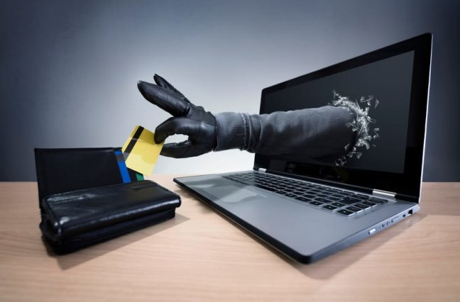 cybersecurity thieves hand breaking through laptop screen to steal credit card