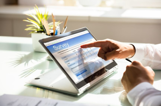 businessman filling online survey form on laptop