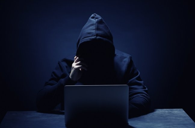 mystery person wearing hoodie in front of laptop