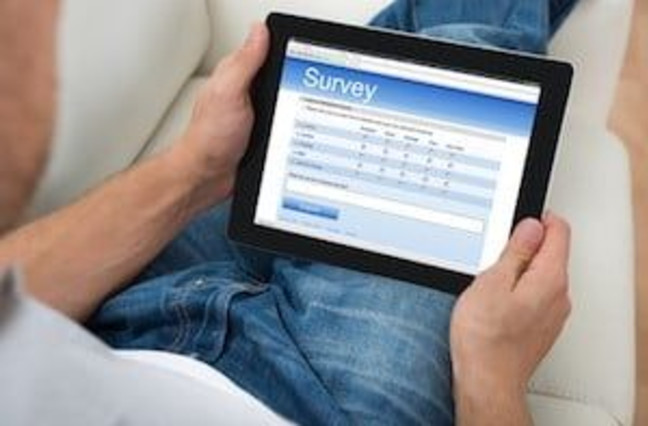 man sitting on couch taking online survey on tablet
