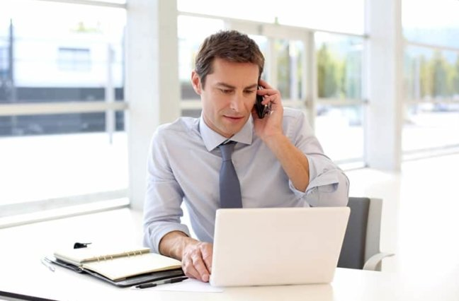 business man on the phone in front of laptop