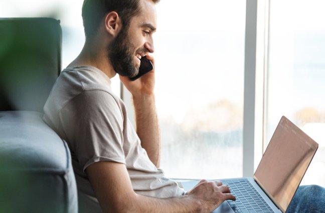 Man talks on phone while using laptop