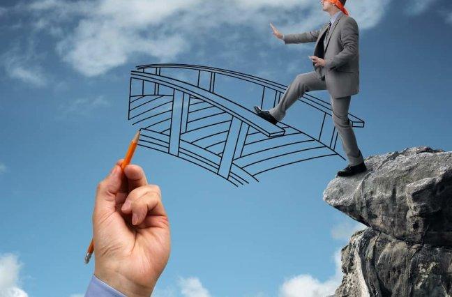 blindfolded businessman walking onto drawing of bridge