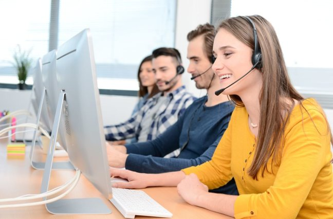 portrait of beautiful and cheerful young woman telephone operator with headset working on desktop computer in row in customer service call support helpline business center with co-worker in background