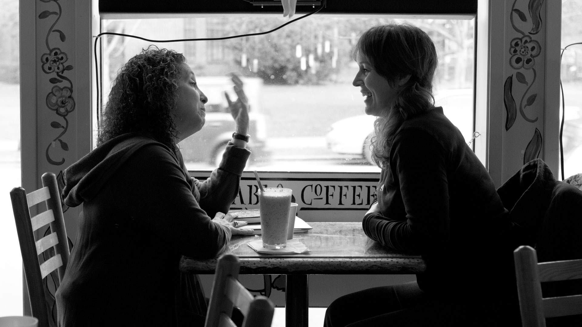 Two people having a conversation in a cafe.