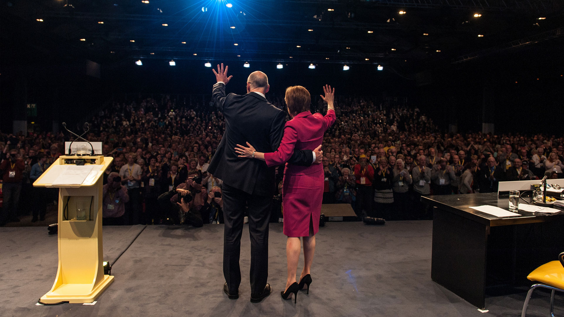 The First Minister of Scotland, Nicola Sturgeon, with Deputy First Minister, John Swinney, waving to the crowd at the 2015 SNP Conference.