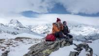 Un couple fait une pause lors d'une randonnée hivernale sur le Gornergrat au-dessus de Zermatt
