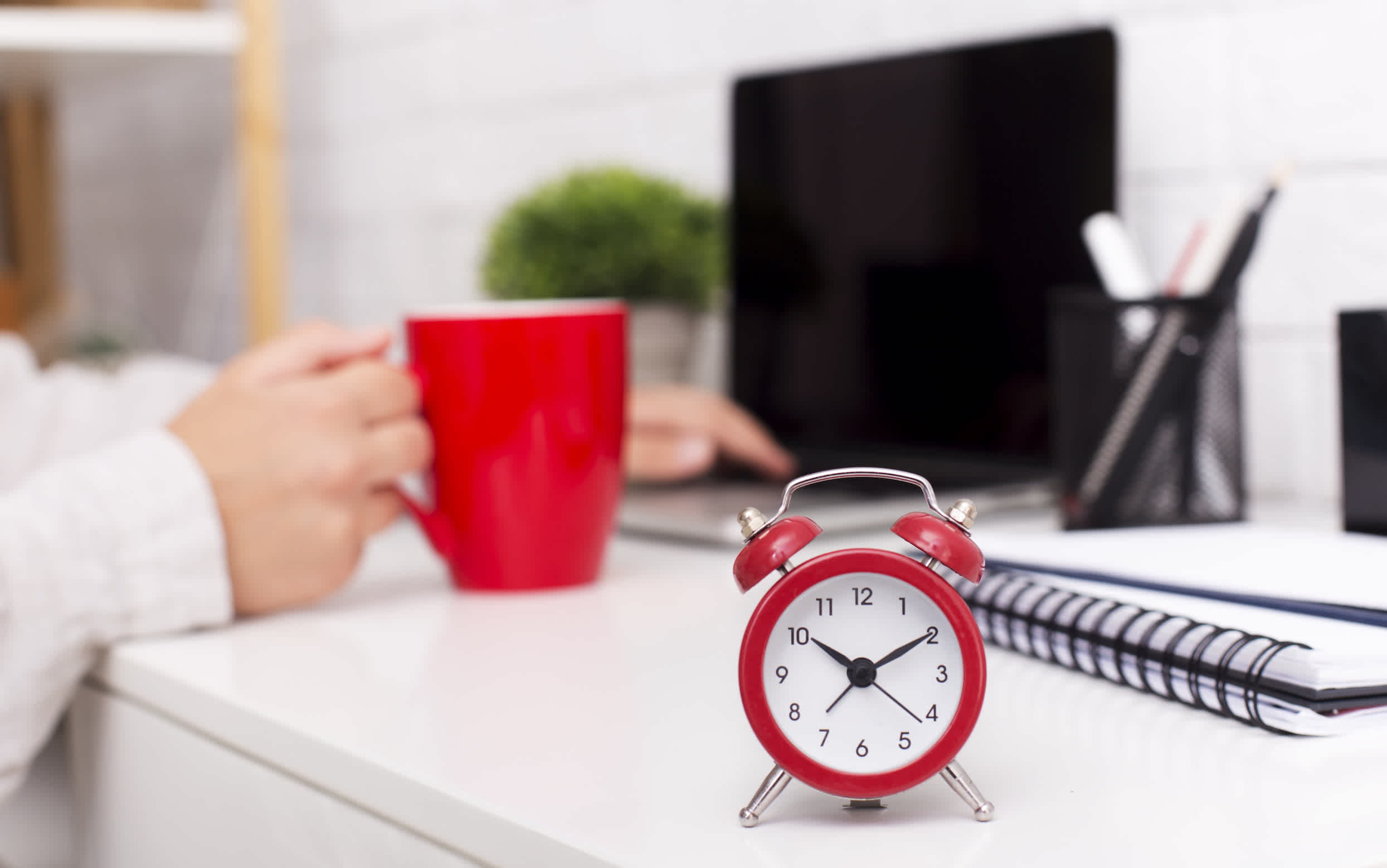 Time management concept. Red alarm clock and morning cup of coffee on office table, panorama