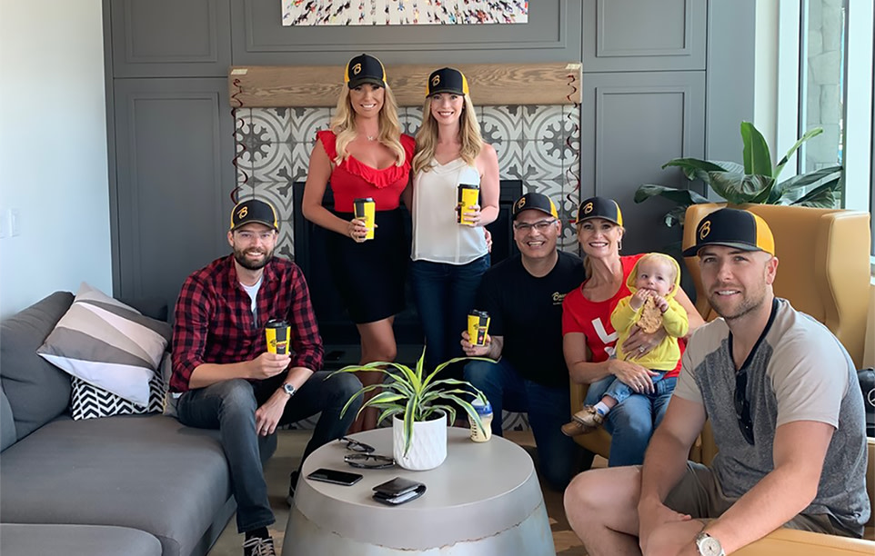 Group fo friends and family smile while holding coffee cups