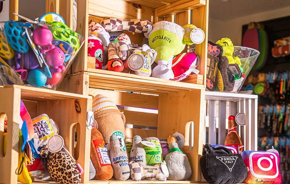 A shelf full of various colourful dog toys