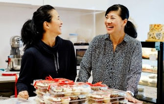 Two women in front of cupcakes