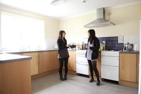 International students talking in a shared kitchen in Willow Walk student residences