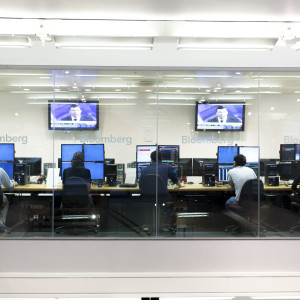 Five INTO Students work on large four screen computers at Bloomberg  as part of BSc Investment and Financial risk management
