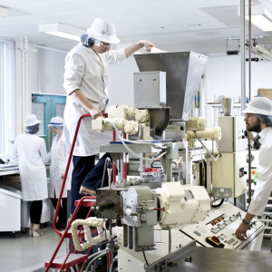 Students using a piece of machinery used during the production of food