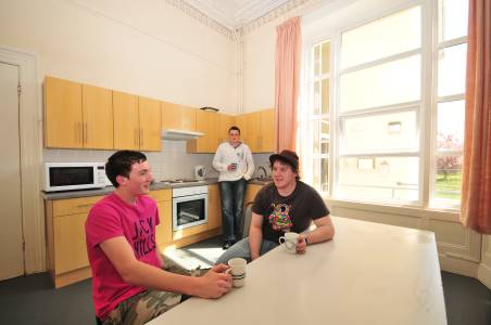 Students talking in a shared kitchen in Eildon Annexe student residences