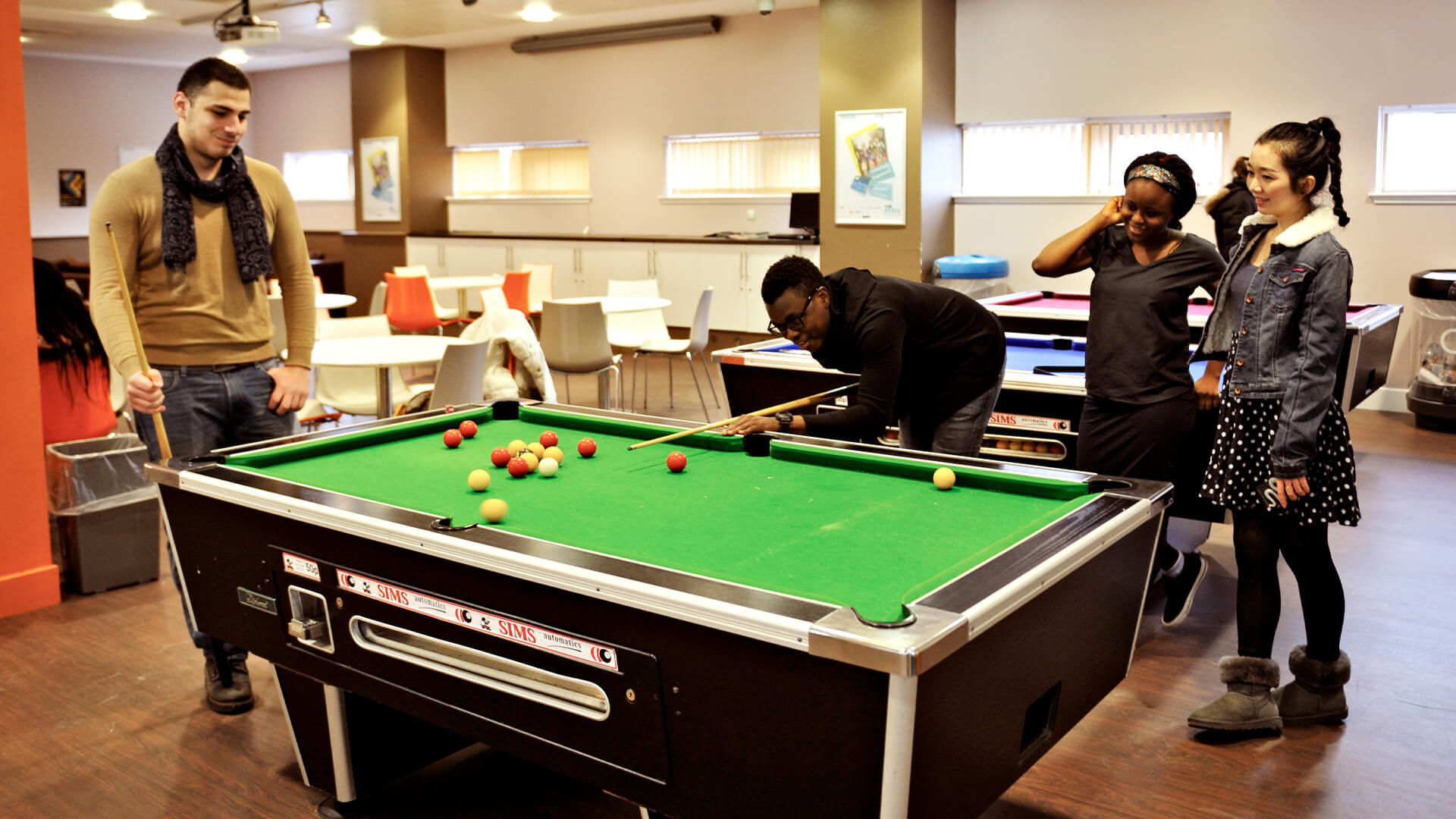 Students socialising and playing pool at Glasgow Caledonian University