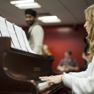 Student playing the piano with sheet music on a music course
