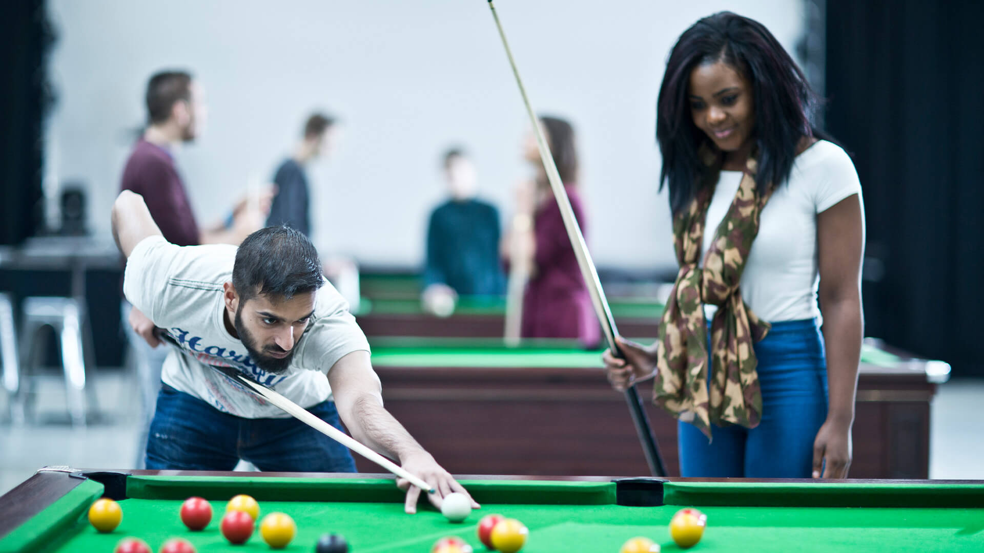 Students playing pool in a breakout area on Manchester Metropolitan University campus