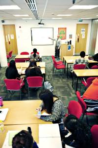 INTO teacher teaching international students in classroom with whiteboard