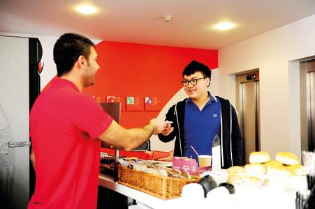 International student being helped by staff at the INTO cafe