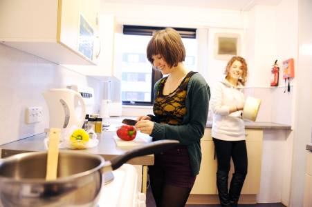 Students cooking in shared kitchen space in John Forty's Court student residences