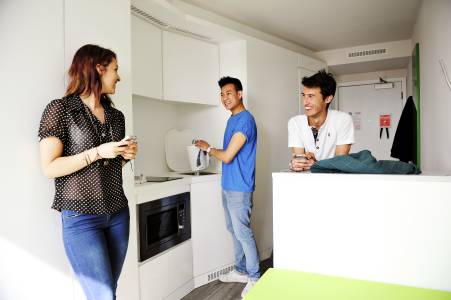 Students socialising in a private kitchen area in Scape East Studio+ accommodation