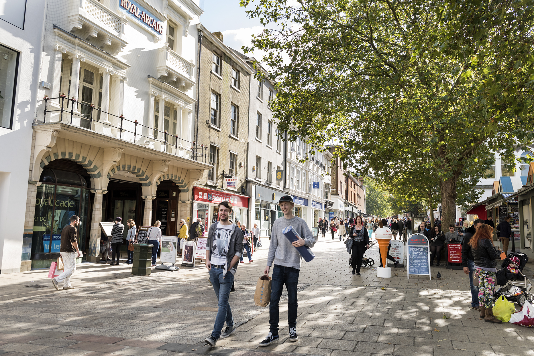 People walking along a street in Norwich during the day
