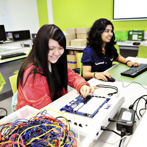 Two INTO International students in an Electronics lab, one studying on a computer the other on an electrical unit