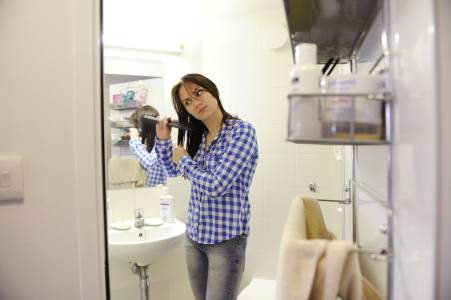 Student straightening her hair in an en suite bathroom in INTO UEA student residence