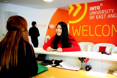 International student talking to staff at the INTO Centre welcome desk