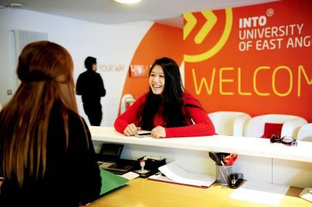 国际学生在INTO中心前台与员工交谈