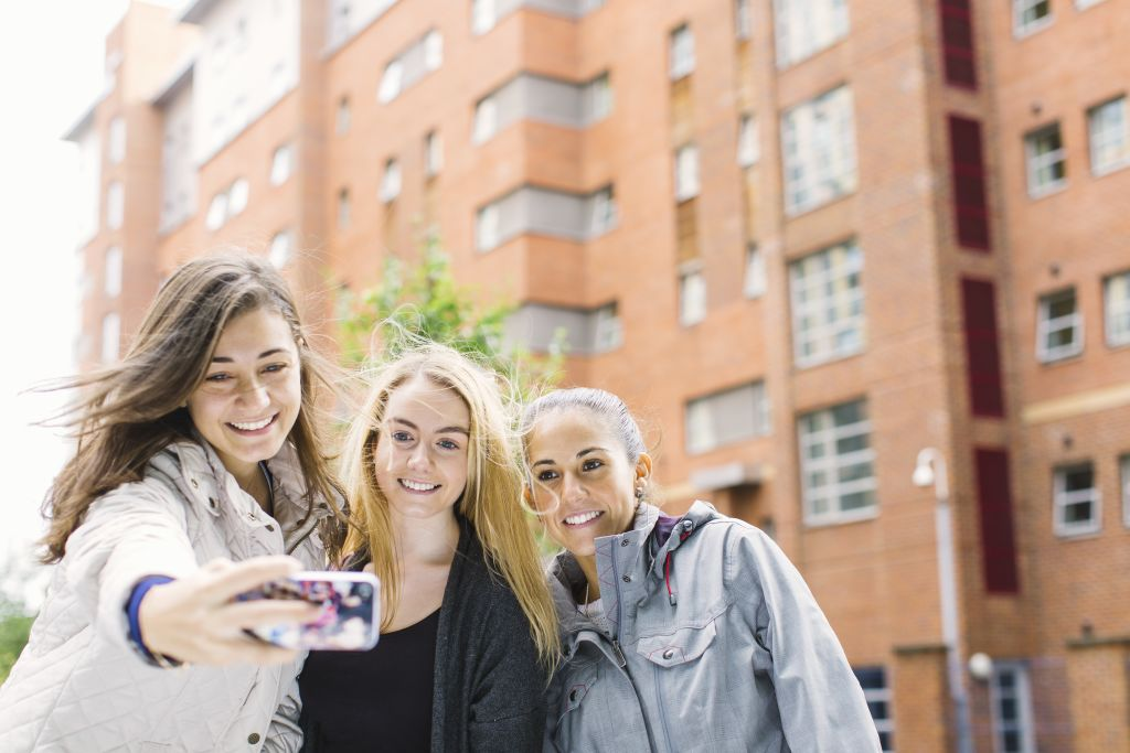 Students taking a photo outside INTO Manchester accommodation