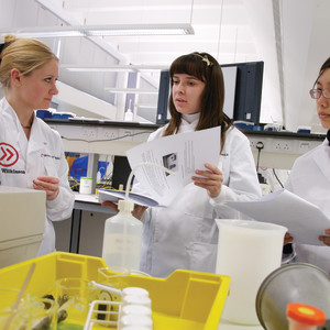Students in lab coats with equipment in lab.