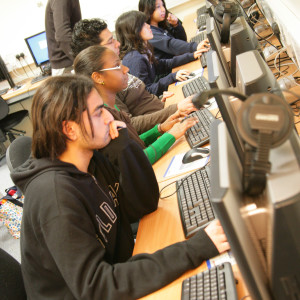 Students in class working on computers as teacher looks over projects