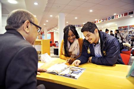 International students at the INTO Centre reception desk looking at University booklet