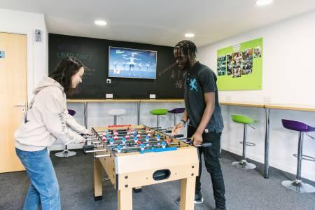 国际学生在Liberty Point公寓休闲区玩桌上足球