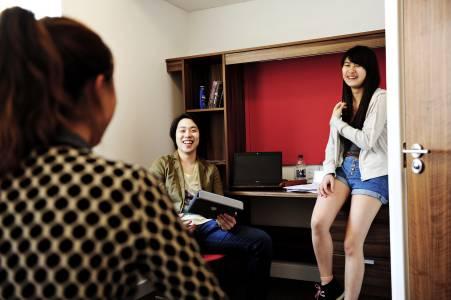 国际学生在Craft公寓卧室内使用笔记本电脑