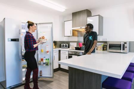 学生在INTO曼彻斯特Liberty Point公寓共享厨房交谈和进食