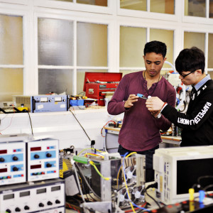 Two INTO International students with several pieces of electrical equipment
