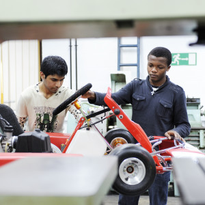 Two INTO International students work on a go kart in a mechanics garage