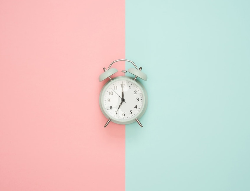 Alarms clock on pink and green background