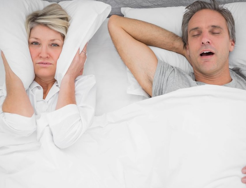 Woman using pillow to block snoring noise from man