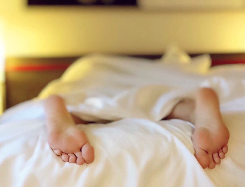 person sleeping face down on bed