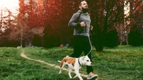 Man running with dog in park