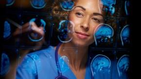 Doctor in blue scrubs looking at brain scans