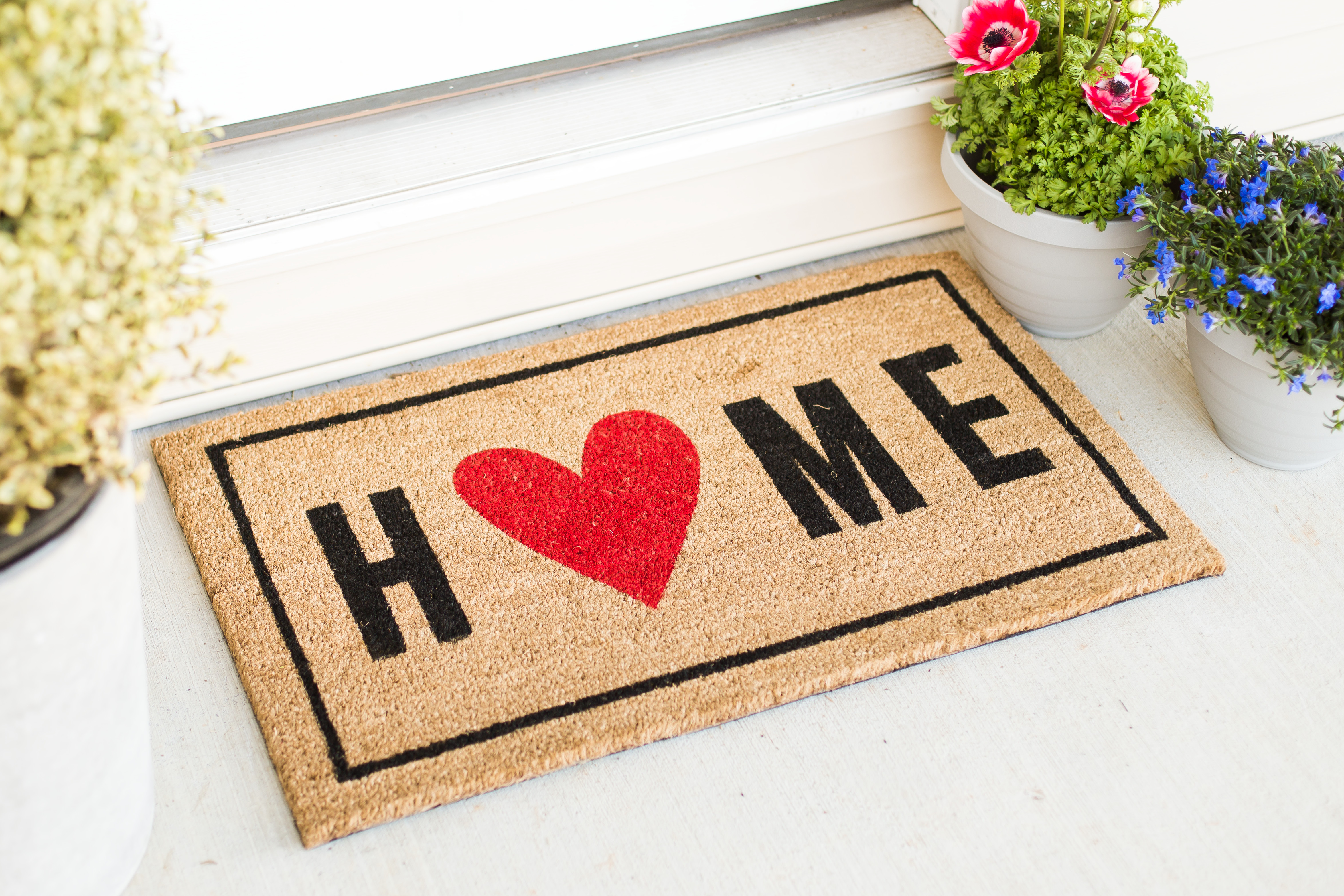 A welcome mat that reads HOME with potted plants beside it.