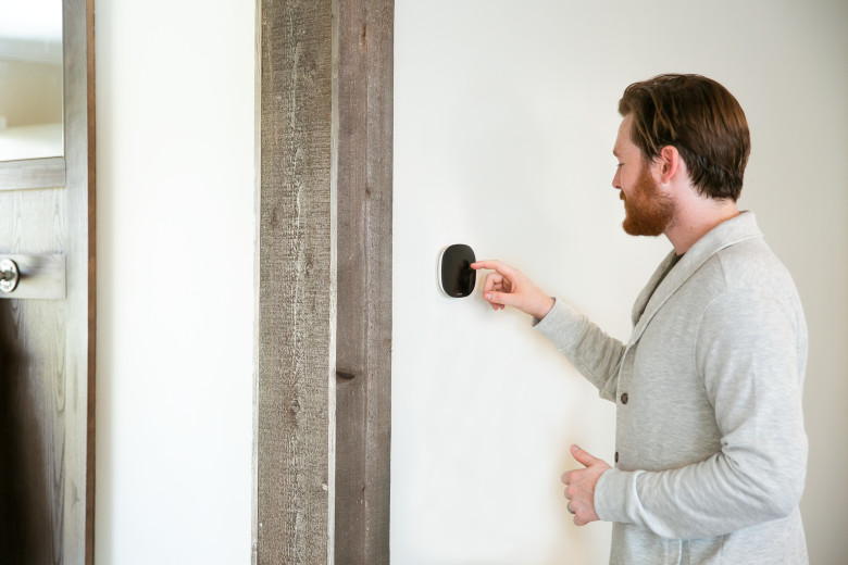 Man adjusting the temperature on the ecobee thermostate in a manufactured home